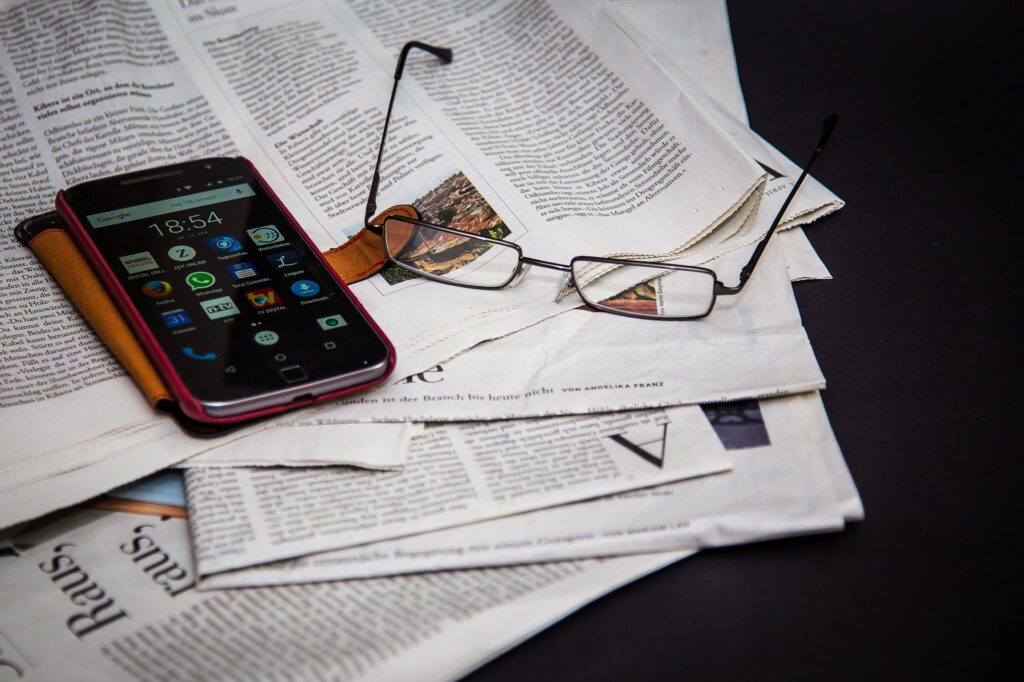 A mobile phone and a pair of glasses on top of a bunch of newspapers - website traffic